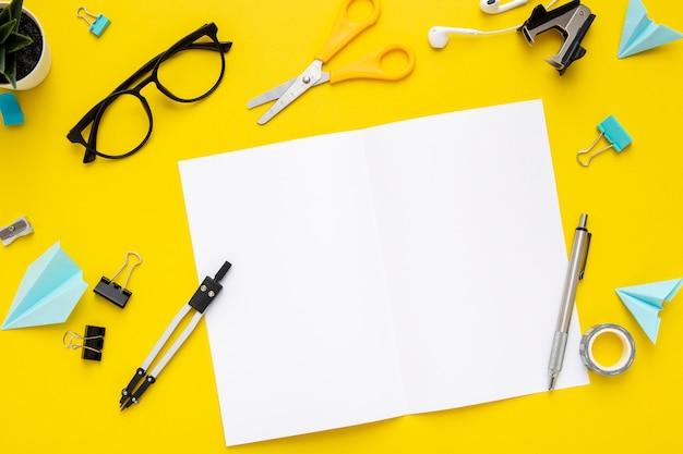 Disposición de papelería plana sobre fondo amarillo con cuaderno vacío