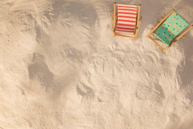 Disposición de pequeñas tumbonas decoradas sobre arena.