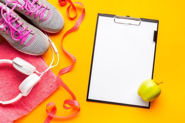 Disposición plana con artículos deportivos, portapapeles y manzana.