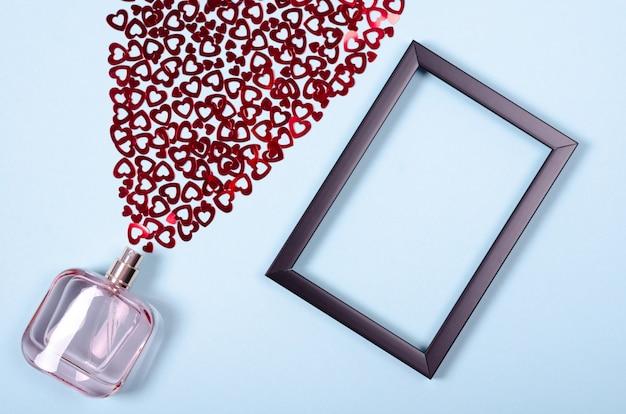 Disposición plana de corazones y frasco de perfume para maqueta.