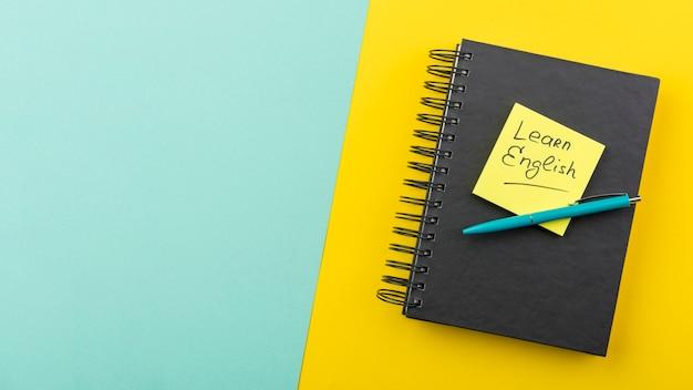 Disposición plana con cuaderno y bolígrafo