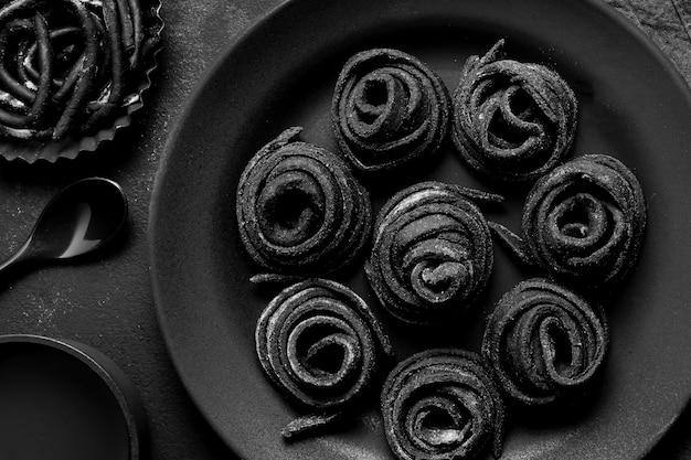 Disposición plana de deliciosa comida negra en plato oscuro y mesa