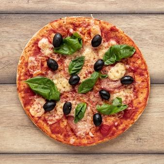 Disposición plana con deliciosa pizza y fondo de madera.