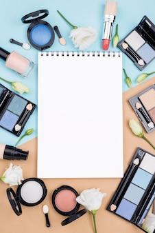 Disposición plana de diferentes productos de belleza con libreta vacía