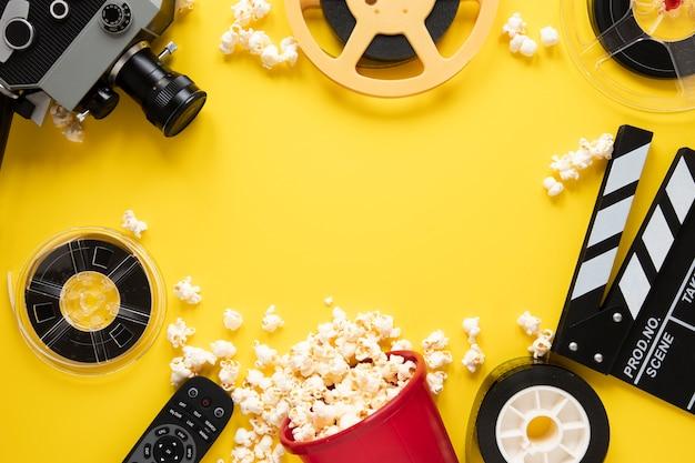 Disposición plana de elementos de cine sobre fondo amarillo con espacio de copia