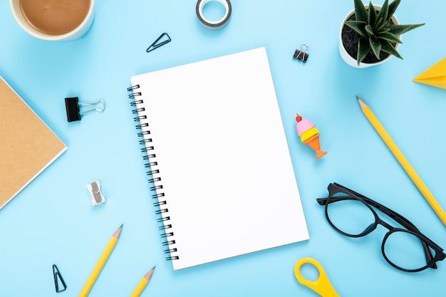 Disposición plana de elementos de escritorio sobre fondo azul.