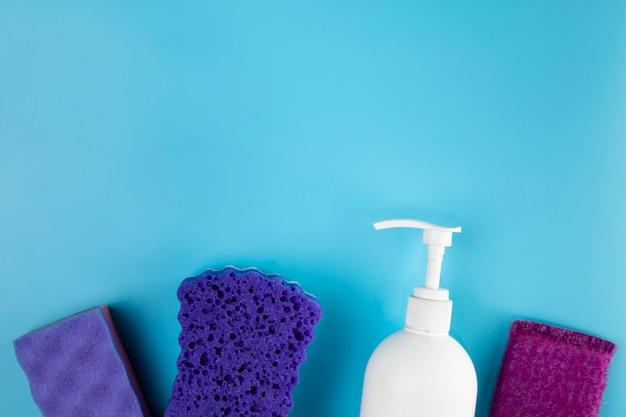 Disposición plana con esponjas moradas y botella de jabón.