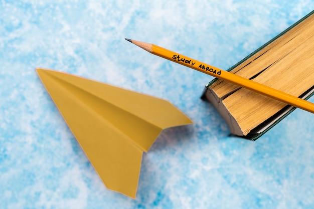 Disposición plana con libro, lápiz y avión de papel.