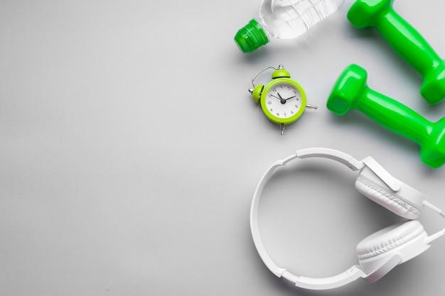 Disposición plana con mancuernas verdes y espacio de copia