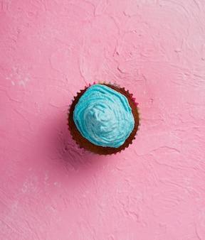 Disposición plana con muffin sobre fondo rosa