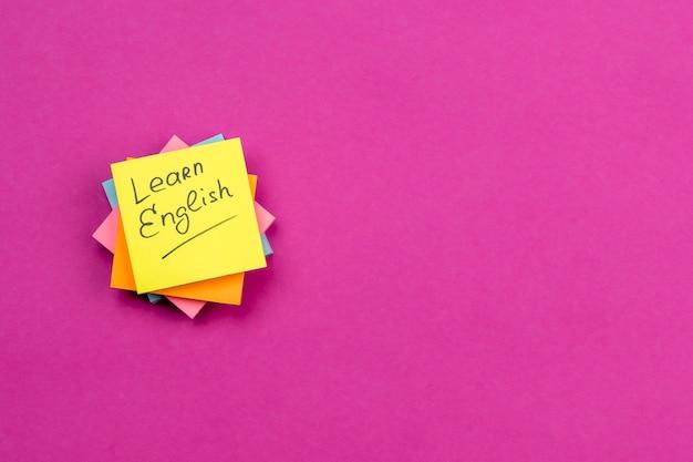 Disposición plana con notas adhesivas sobre fondo rosa