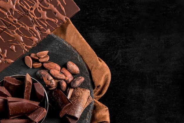 Disposición plana y oscura con chocolate y espacio de copia