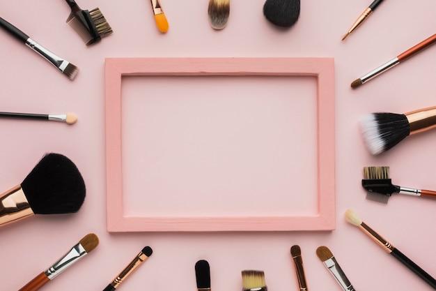 Disposición plana con pincel de maquillaje y marco rosa