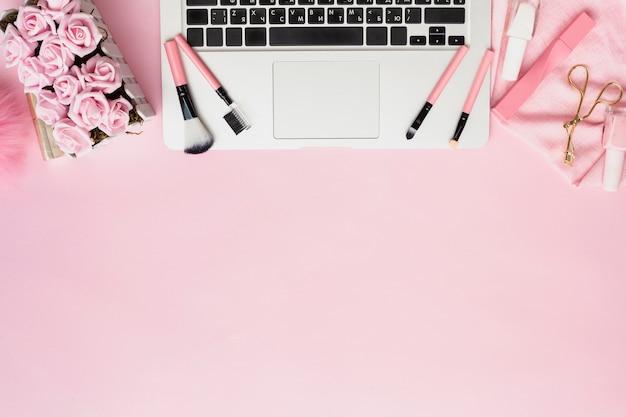 Disposición plana con pinceles de maquillaje en la computadora portátil