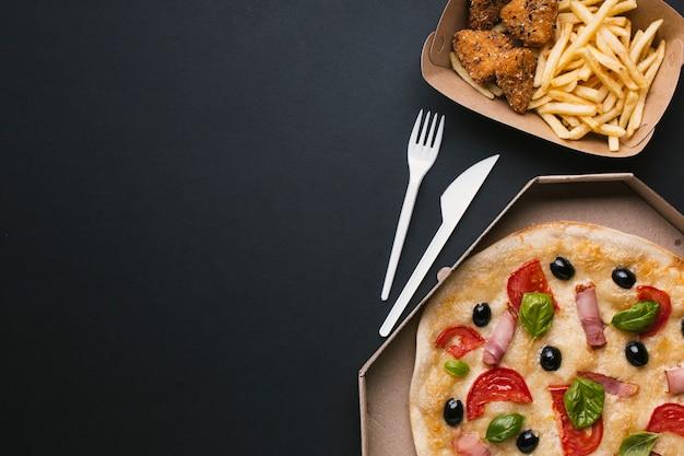 Disposición plana con pizza y comida rápida.