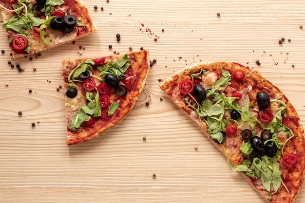 Disposición plana con pizza y fondo de madera.