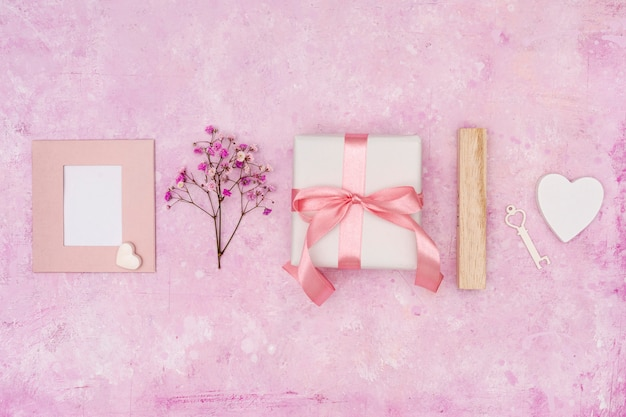 Disposición plana con presente sobre fondo rosa