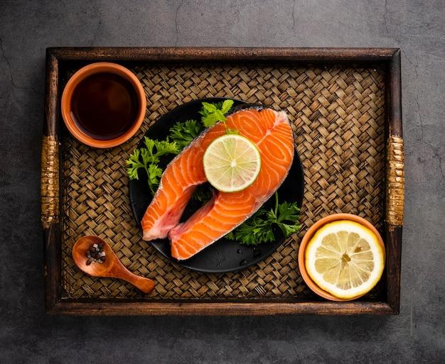Disposición plana con salmón y limón.