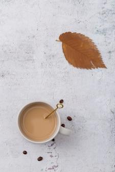Disposición plana con taza de café y hoja