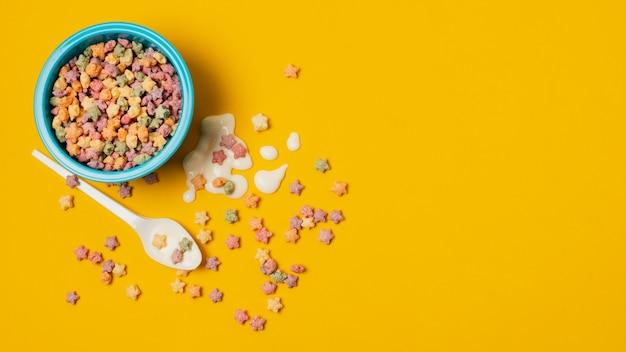 Disposición plana con tazón de cereal sobre fondo amarillo