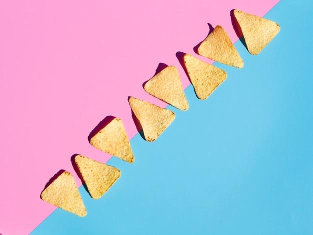 Disposición plana con tortilla sobre fondo rosa y azul