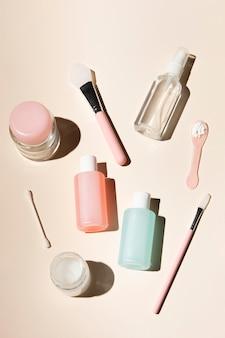 Disposición de productos para el cuidado corporal sobre fondo rosa polvo