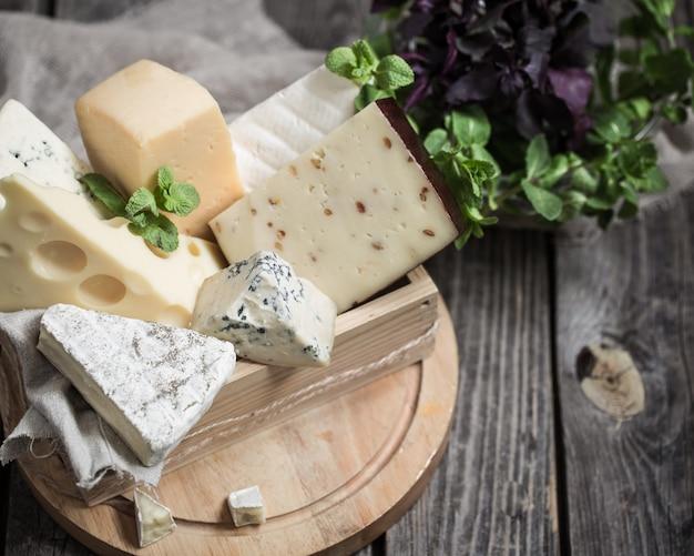 Disposición de queso gourmet sobre fondo de madera, concepto de quesos gourmet