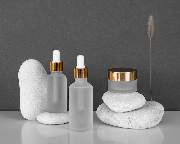 Disposición de recipientes de crema facial y goteros de aceite para la piel