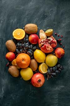 Disposición de selección de frutas frescas planas sobre una superficie grunge como uvas, kiwi, naranja, frutas tropicales exóticas