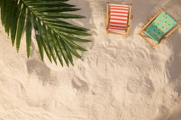 Disposición veraniega de la hoja de palmera y las pequeñas tumbonas sobre y