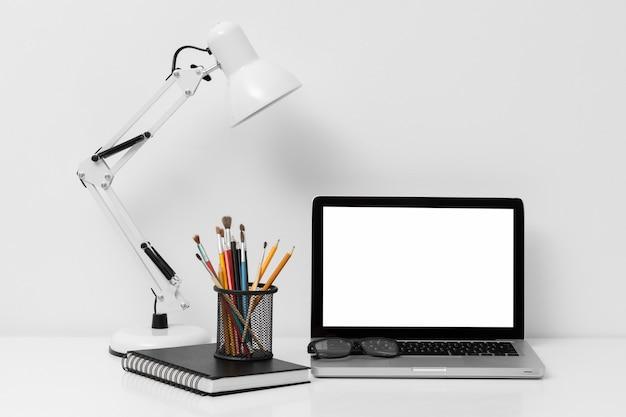 Disposición de vista frontal de elementos de oficina con portátil