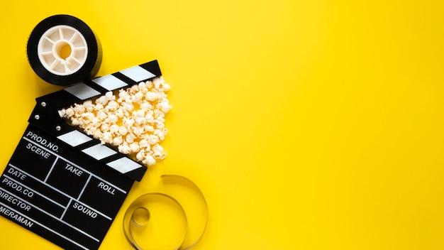 Disposición de la vista superior de elementos de cine sobre fondo amarillo con espacio de copia