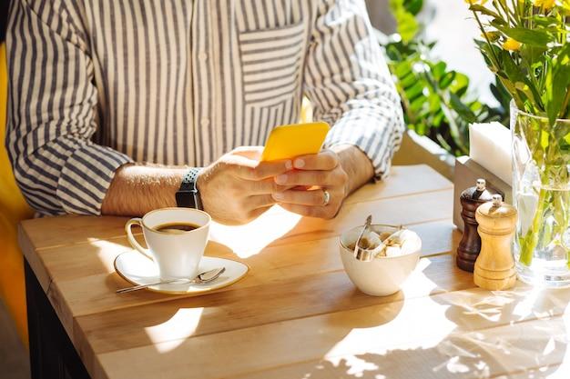 Dispositivo digital. cerca de manos masculinas con smartphone moderno en ellos