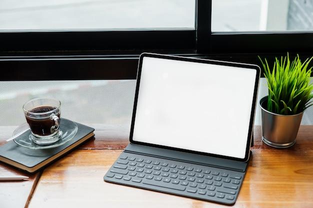 Dispositivo digital de la tableta de la pantalla en blanco de la maqueta en la tabla de madera en espacio de co-working.
