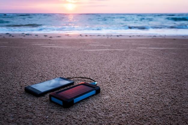 Dispositivo de energía solar de batería sobre un fondo de la playa de arena de una isla deshabitada. cargue el teléfono inteligente con la batería solar. hermoso atardecer o amanecer tropical. electrónica de protección contra el agua