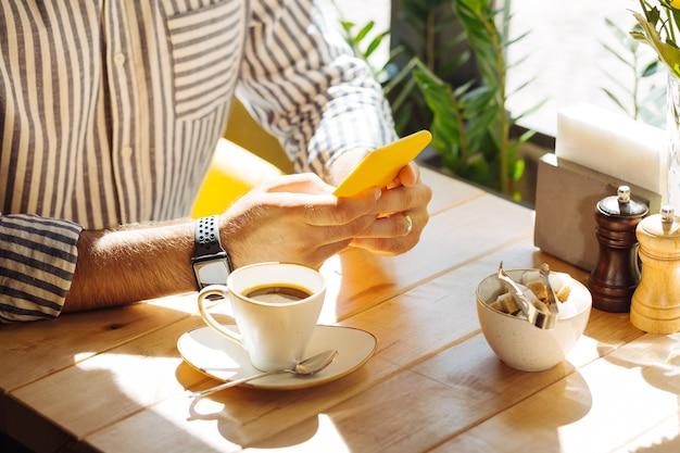 Dispositivo moderno. cerca de un teléfono inteligente en manos masculinas mientras está sentado en la mesa de la cafetería