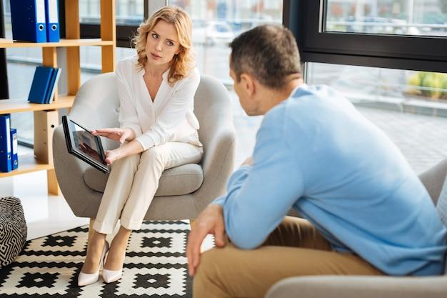 Dispositivo moderno. doctora agradable profesional sosteniendo una tableta y hablando con su paciente mientras tiene una sesión de terapia con él
