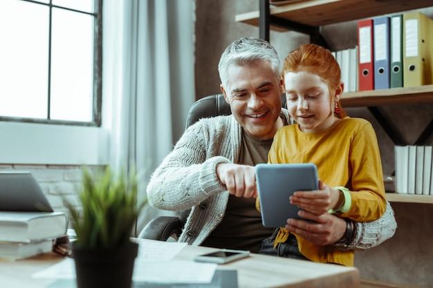 Dispositivo moderno. hombre positivo alegre presionando la pantalla de la tableta mientras muestra el dispositivo a su hija
