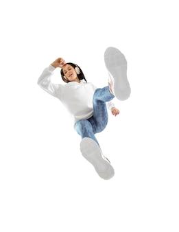Dispositivo. mujer joven con estilo en traje moderno estilo callejero aislado en superficie blanca, disparó desde la parte inferior. modelo de moda caucásico en zapatos y monos, músico, rapero.