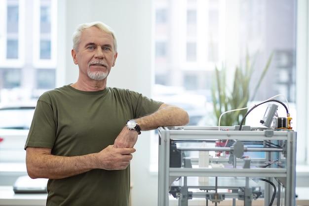 Dispositivo nuevo. hombre mayor optimista posando cerca de una impresora 3d y sonriendo mientras apoya su codo en ella