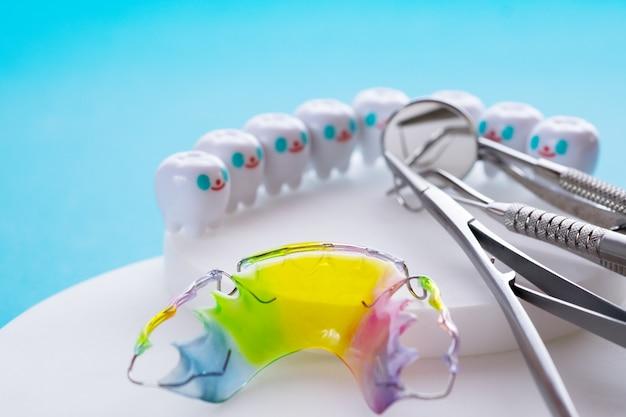 Dispositivo de ortodoncia retenedor dental y herramientas dentales en el fondo azul.