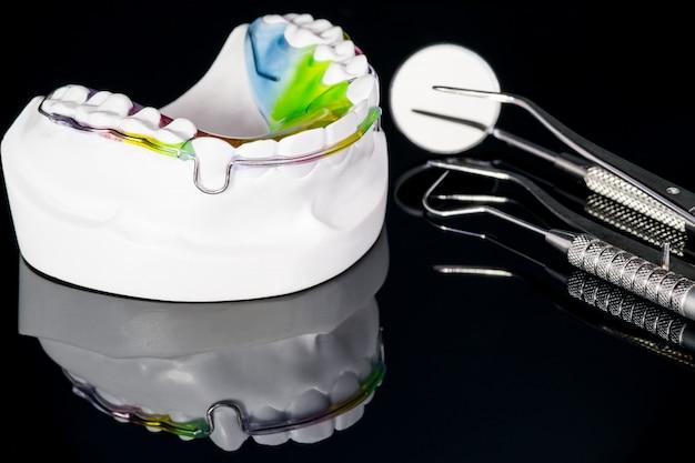 Dispositivo de ortodoncia retenedor dental y herramientas dentales sobre el fondo negro.