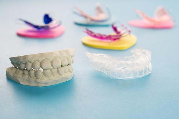 Dispositivo ortodóntico del criado dental en el fondo azul.