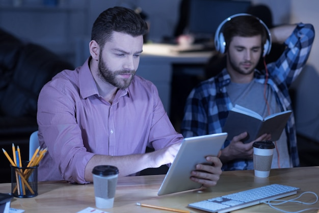 Dispositivo portátil. programador barbudo guapo serio sosteniendo una tableta y trabajando en ella mientras está en la oficina
