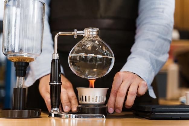 Dispositivo de primer plano de café con sifón con fuego calienta el matraz de vidrio en el café