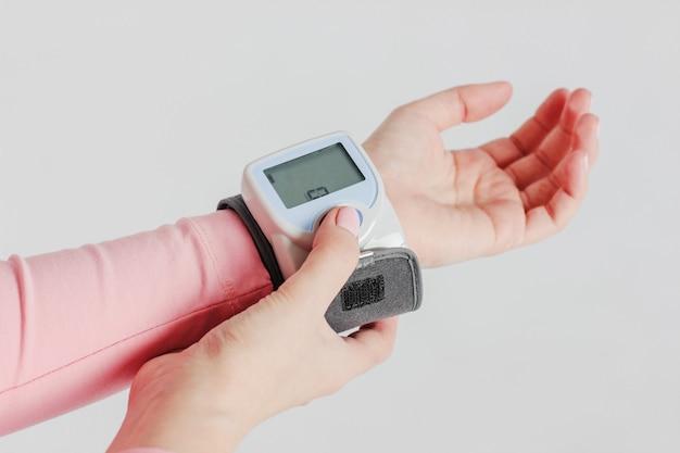 Dispositivo tonómetro para medir la presión sanguínea en la mano de la mujer.