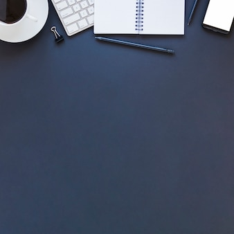 Dispositivos electrónicos portátil y taza de café en la mesa azul oscuro