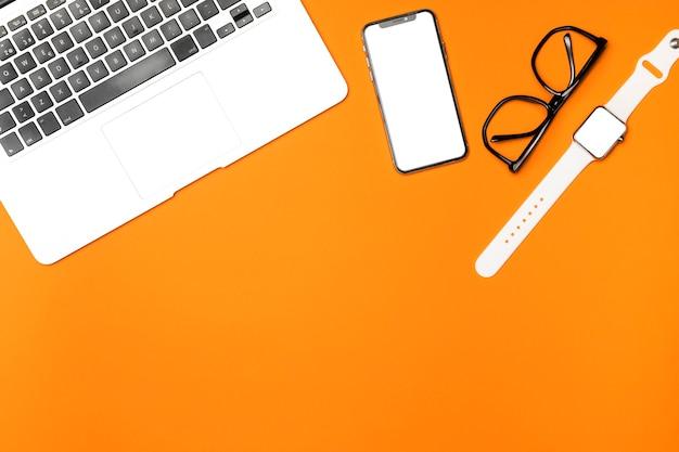 Dispositivos de maqueta de vista superior con fondo naranja