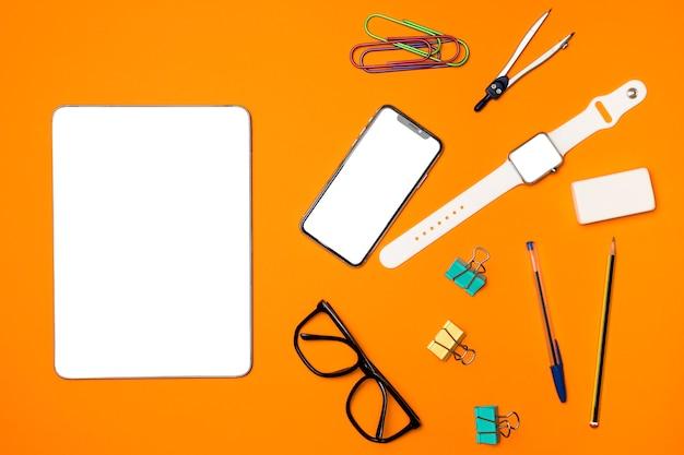Dispositivos de maqueta de vista superior con suministros de oficina