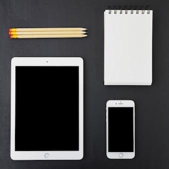 Dispositivos tecnológicos, libreta y lápices